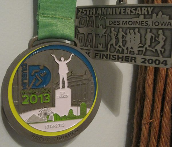"There it is. My Dublin Marathon finisher medal, hanging on my ""medal tree"" next to the finisher medal from my very first distance race - the 20K Dam to Dam in Des Moines, Iowa."