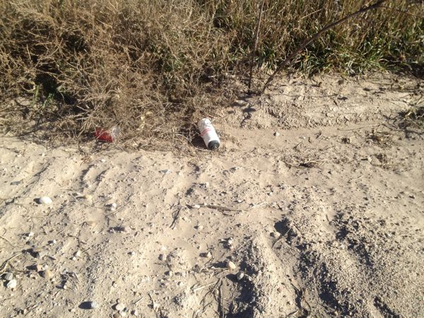 Aha! The object of my mission, next to a red plastic cup! Kind of surprised it was still there, but kind of not. There were lots of other beverage containers out there in the ditches. Beer cans and bottles, mostly. I suspect underage people drive on the gravel roads outside of town at night, drinking and ditching the evidence. *sigh*