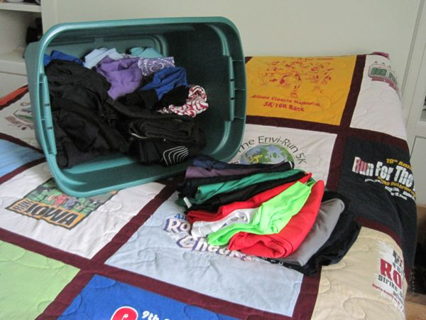 Short-sleeved shirts piled on the bed, cold-weather gear stacked in the storage tub. (The quilt on my bed was made from years worth of running shirts from my time in Iowa.)