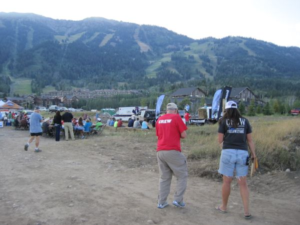 A volunteer and Assistant Event Director confer about course details as a presentation is underway onstage at Teton Village. Every night, there is a presentation about some aspect of the Greater Yellowstone ecosystem and the challenges it faces, as well as updates on logistics for the following day's ride.