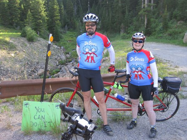 "Made it around a bend to a flatter area when a waterfall drizzled through underneath the road. The ride organizers had placed an encouraging sign. There was a hint of ""yeah, right"" in my smile."