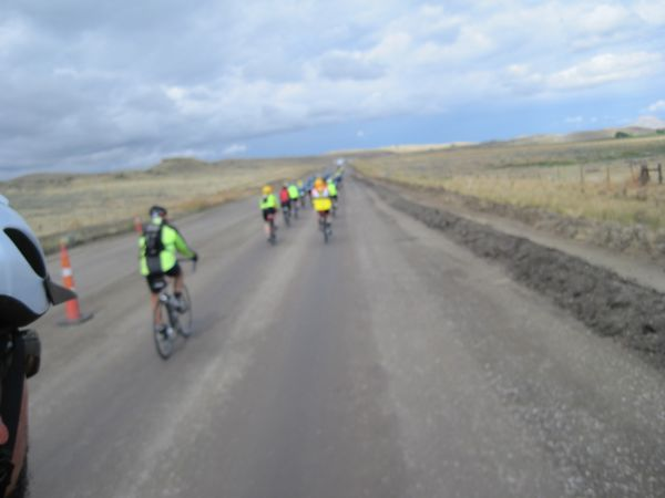 A view forward of the pack of cyclists on a packed-dirt section of the road. (Dumb camera decided to focus on the edge of Bugman's helmet instead of the riders ahead. Thank GOODNESS it was not raining when we went through here!