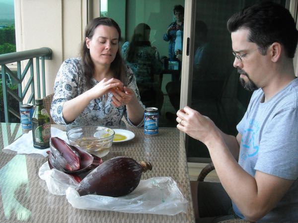 Working on processing the banana blossom. Per online advice, we slathered olive oil on our hands to prevent the sap from staining our fingers. We both tasted the banana flowers as we worked - YUK! Bitter! Astringent! Can this really be edible?? Hooboy. This may be a lot of work for nothing. (Photo by Ma Bug)