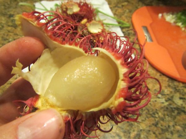 Just peel off the thick, hairy hide off a rambutan to get at the fruit inside, which has a kind of gummy texture. The seed, which you have to eat around, reminds me of the seed of a mango in how it clings to the fruit's flesh.