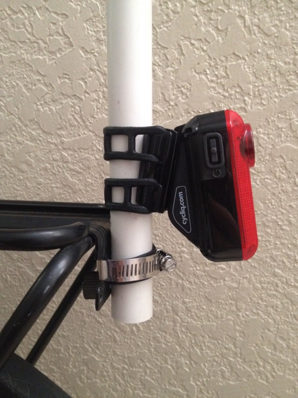 We attached a length of PVC pipe to the light mount on the pannier rack by drilling a hole through the PVC and attaching it through the light mount with a screw (prevents sliding down) and adding a pipe clamp higher up (prevents sideways torque).